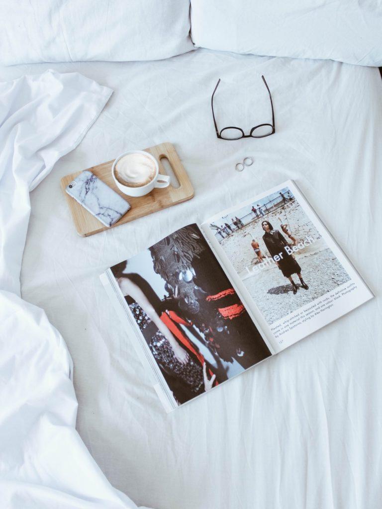 Okulary, magazyn, kawa na łóżku