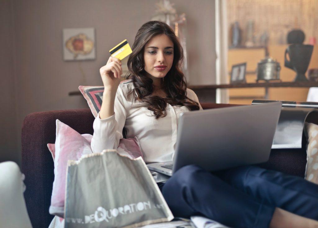 Brunetka trzymająca kartę kredytową z laptopem na kolanach