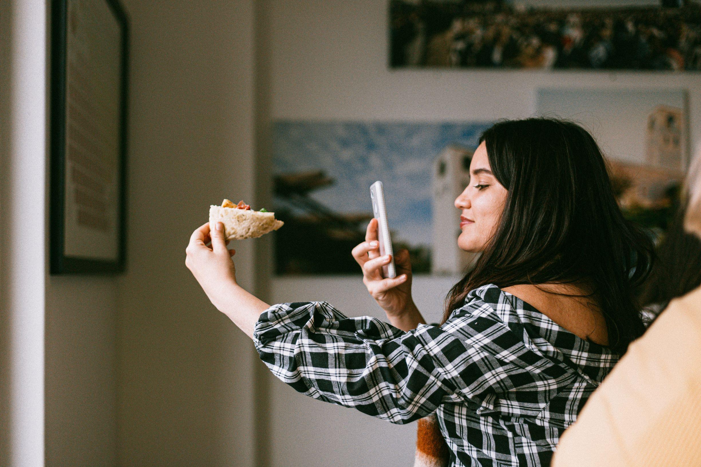 Kobieta robiąca zdjęcie pizzy