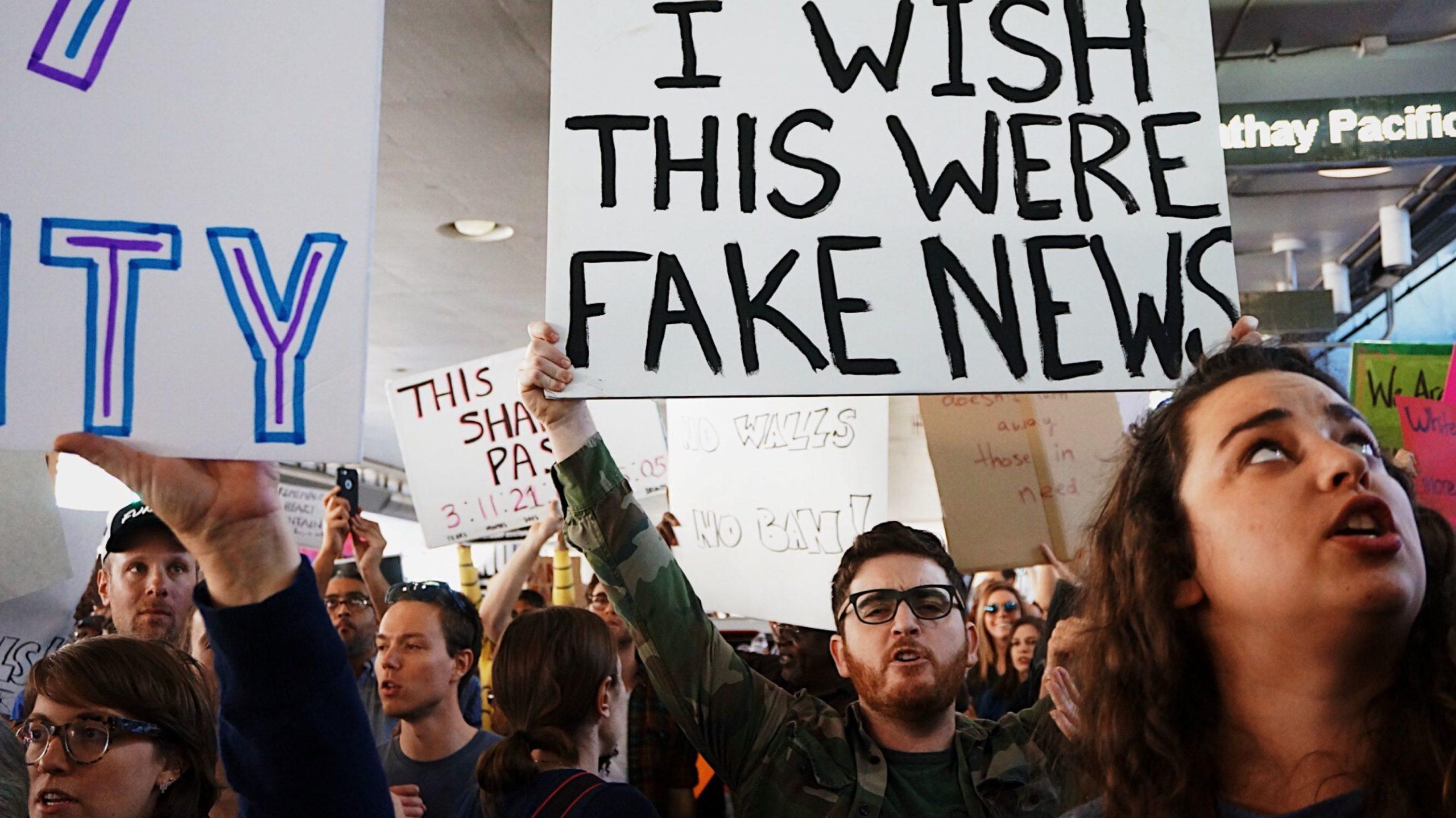 ludzie na demonstracji, mężczyzna trzyma transparent z napisem fake news