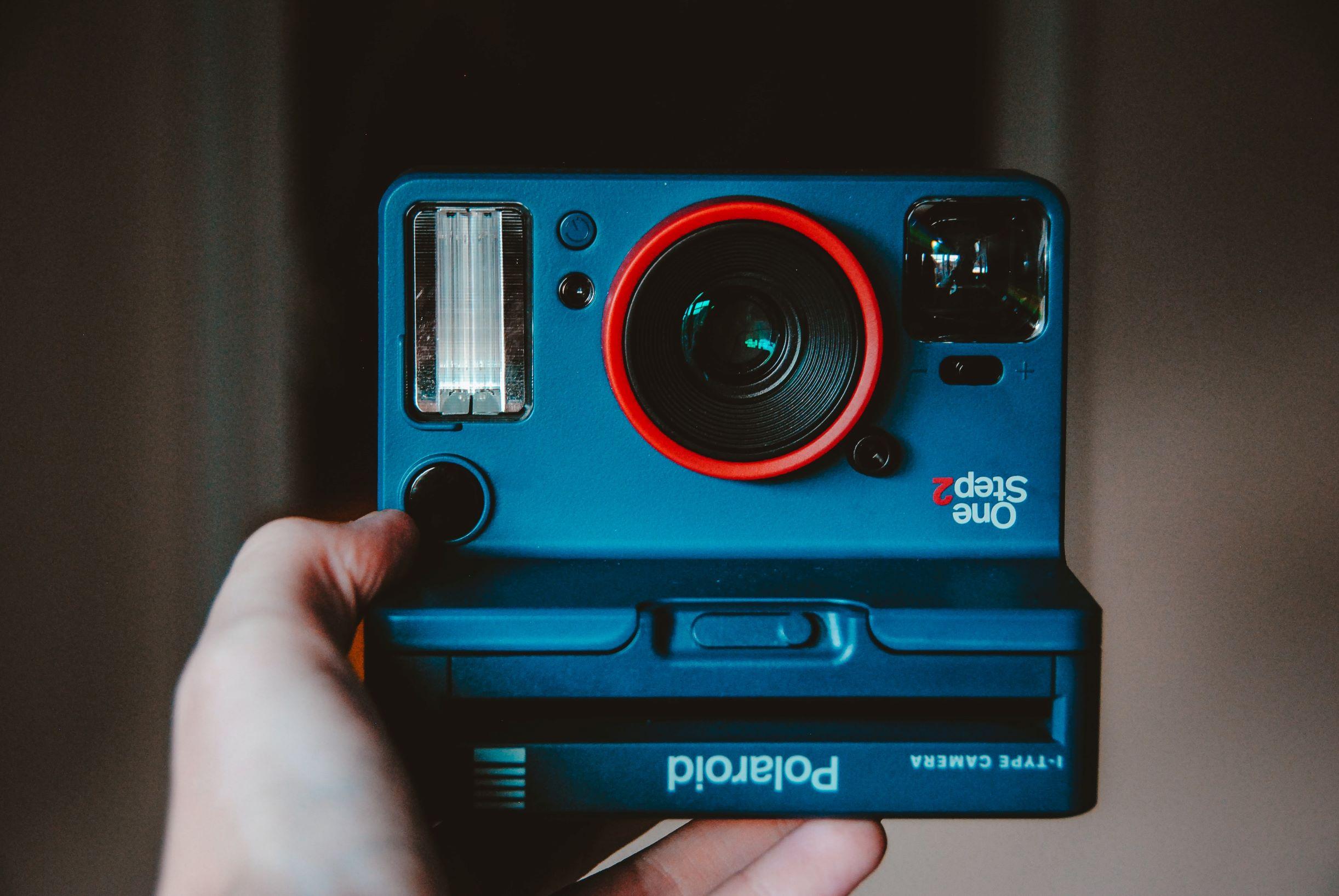 ręka trzymająca czarny aparat polaroid