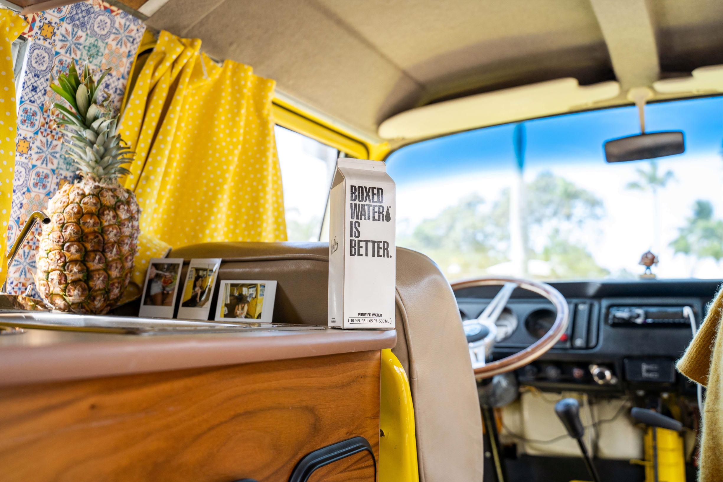 wnętrze campera, na komodzie stoi biały karton z czarnym napisem boxed water is better