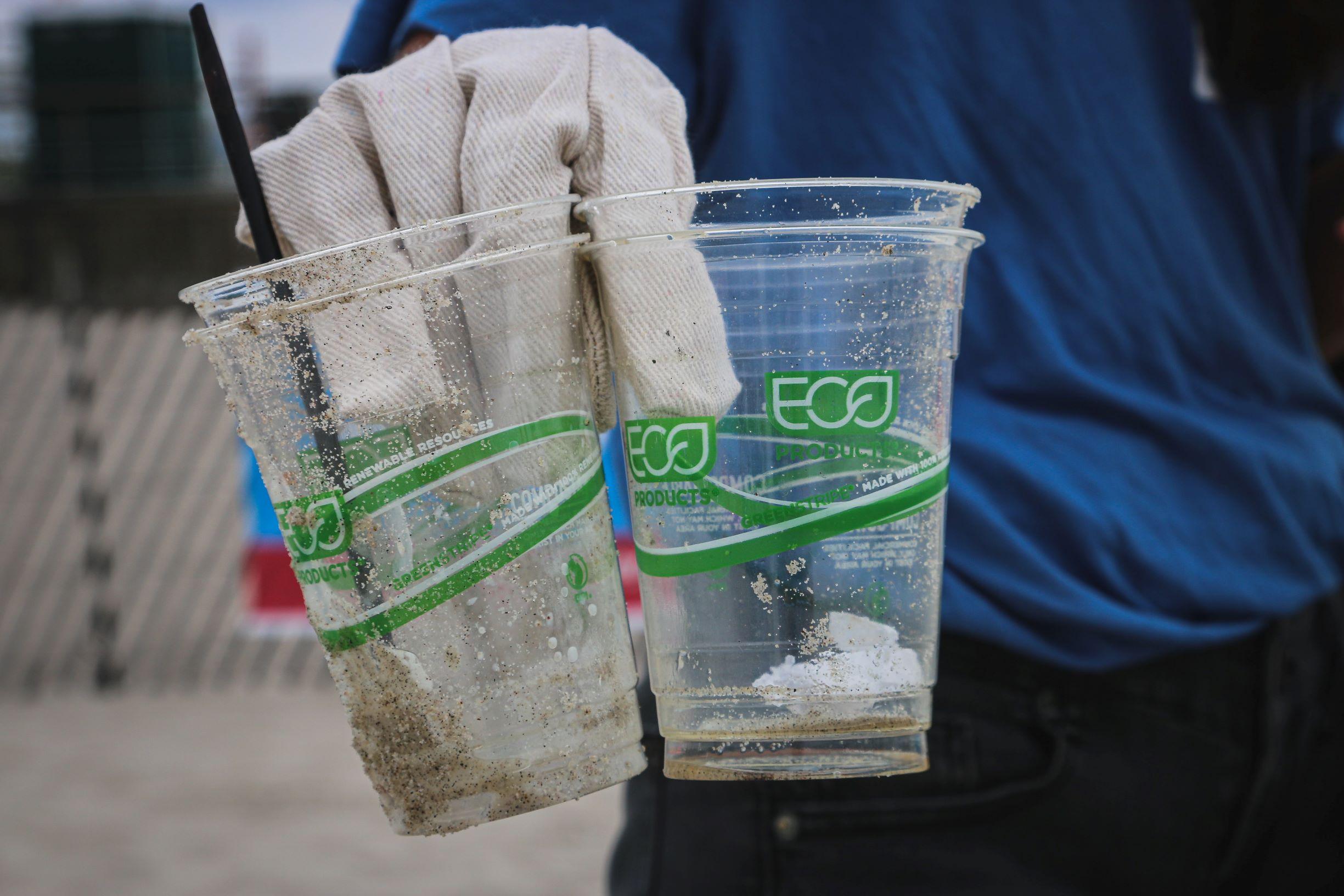 ręka w rękawiczce trzymająca zużyte opiaszczone kubki z napisem eco